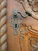 stock photo of carving  - decorative handle on the old beautiful carved door - JPG