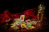 pic of occult  - A pile of tarot cards lie scattered and spread across a table top surrounded by multiple occult items - JPG