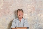 picture of rotten  - portrait of senior man in front of grungy old wall in a rotten house - JPG