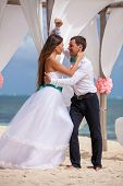 stock photo of wedding arch  - young loving couple on their wedding day beautiful wedding arch on beach outdoor beach wedding in tropics - JPG