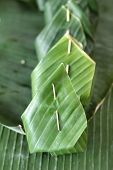 stock photo of custard  - Sticky rice with custard wrapped in banana leaves - JPG