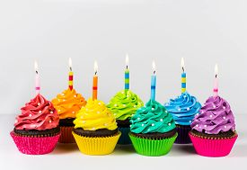 stock photo of icing  - Rows of colorful cup cakes decorated with birthday candles and sprinkles - JPG