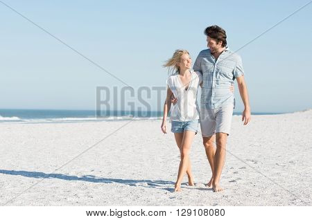 Young couple embracing and walking at the beach on a bright sunny day. Couple in love holding hands