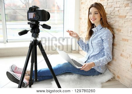 Young female blogger with laptop recording video at home