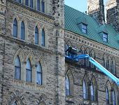 stock photo of cherry-picker  - workers repairing canadian government building in cherry picker - JPG