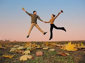 jump couple. autumn leaves. sunset sky