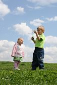 Kinder mit Seifenblasen auf Wiese