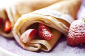 stock photo of crepes  - sweet thin french style crepes served with strawberries and castor sugar very close up and very shallow dof for a dreamy effect focus on the strawberry in front - JPG