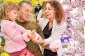 family with little girl buy milk in supermarket