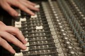 sound producer moving fads of dirty sound mixer panel. focus on fingers of right hand