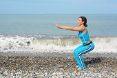 joyful woman wearing sporty clothes is making exercise on sea coast. she is squating.
