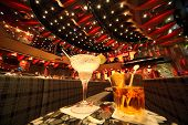 big illuminated hall. coaches and tables. wineglass and glass with drinks in center of image. focus