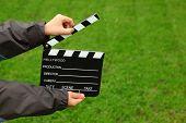 Junta de badajo de cine en manos de niño chaqueta en campo de hierba verde