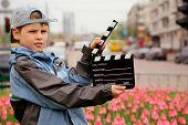 Un muchacho en la chaqueta y gorra con tablero de badajo de cine en manos de pie en el campo con tulipanes urbana