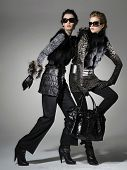 Two fashion model wearing sunglasses holding purse posing