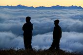 People Contemplating A Sea Of Clouds
