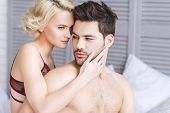 Seductive Young Couple Of Lovers Embracing On Bed poster