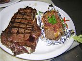 stock photo of baked potato  - just so good clean food fun an onion brush a twist of a red bell pepper on a mediun rare new york strip - JPG