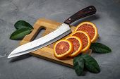 Raw Food: Fresh Juicy Red Orange. Slice Thin Slices On A Cutting Board. poster