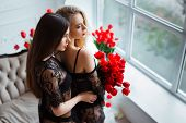 Fashion Models In Tender Black Lingerie Posing In Sensual Way At Luxury Interior Full Of Tulips. You poster