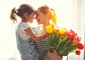 Happy Mothers Day! Child Daughter   Gives Mother A Bouquet Of Flowers To Tulips. poster