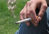 foto of cigarette-smoking  - A hand holding a smoking cigarette  - JPG