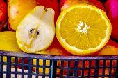 Sliced In Half A Pear, An Orange On Red Apples. Sliced Fruit. poster