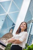 Asian business woman confident in Hong Kong. Businesswoman standing outdoor looking up in hope for f poster