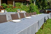 Dinner Table With Empty Ceramic Round Plates And Cutlery On Grey Tablecloth And Chairs Outdoors, Cop poster