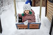 Adorable Child Girl Enjoys Seesaw In Winter