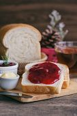 Delicious Toast Bread With Butter And Spread With Strawberry Jam Served With Hot Tea On Wood Cutting poster
