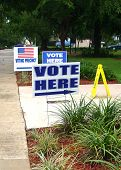 stock photo of poll  - Voting place signs on sidewalk to the entrance of a polling location - JPG
