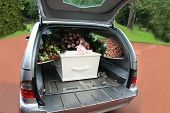 stock photo of hearse  - A white coffin covered with flowers in a grey hearse - JPG