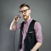 Karaoke Man Sings The Song To Microphone, Singer With Beard On Grey Background. Funny Man In Glasses poster