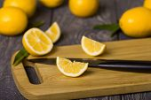 Whole Citrus, Sliced Lemon Slices And Knife On Cutting Board, On Wooden Table poster