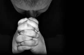 stock photo of piety  - Man pray for something over black background with space for text on right - JPG