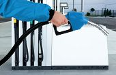 Hand is holding blue gasoline pistol pump fuel nozzle on gas station poster
