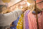 Woman Hand Choosing Clothes Garment In Mall Or Clothing Store. Colorful Dresses On Hangers In A Reta poster