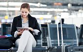 Young female passenger at the airport, using her tablet computer while waiting for her flight (color
