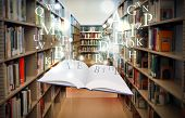 stock photo of floating  - A white book is floating with sparkles and letters in a library isle - JPG