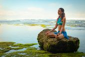 Young Woman Seating On The Rock, Meditating, Practicing Yoga And Pranayama At The Beach, Bali. Hands poster