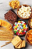 Salty Snacks. Pretzels, Chips, Crackers In Wooden Bowls And Candy And Chocolate On Table poster