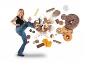 stock photo of junk  - A young woman is kicking donuts on a white background within an assortment of junk food - JPG