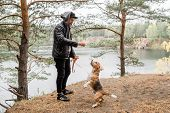 Young man in leather jacket and black jeans giving something tasty to cute purebred beagle puppy dur poster