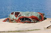 Large Pile Of Heavily Used Fishing Nets Covered With Nylon Protection And Strong Rope Left On Pier E poster