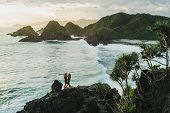 Man And Woman Looking To Each Other With Love At Sunset With Amazing Ocean And Mountain View. Travel poster
