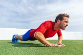 Fitness man doing diamond hand push ups exercises at outdoor grass park. Core body workout athlete p poster
