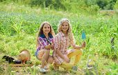 Sisters Together Helping At Farm. Girls Planting Plants. Garden And Beds. Planting And Watering. Rus poster