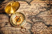 Old vintage retro golden compass on ancient map. The map used is in Public domain. Map source: Libra