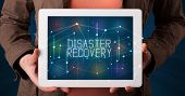 Young business person working on tablet and shows the digital sign: DISASTER RECOVERY poster